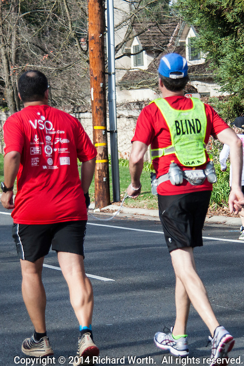 A blind runner, a runner who happens to be blind, passing The Wall at mile 20 of the 26.2 mile CIM 2014 in Sacramento.