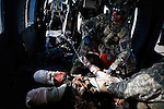 "10/7/2010 Marjah, Helmand Province, Afghanistan.Flight Medic SGT Ian Bugh of Charlie Co. 6-101st prepares to treat a gravely wounded US Marine who lost both of his legs after stepping on a Taliban improvised explosive device, immediately after picking up the wounded marine from the point of injury in southern Marjah, Helmand Province...The Helicopter Medevac teams of Task Force Destiny, based at Forward Operating Base Dwyer in Afghanistan's war-torn Helmand Province have a tough job. Servicing a large area that includes still restive southern Marjah, and much of the Helmand River Valley, TF Destiny answers the call to transport gravely wounded US Marines and Afghan civilians from the point of injury in the field to Role 3 trauma centers on bases in the area--often times landing under fire to extract Marines and soldiers that would otherwise succumb to their wounds. After the Medevac helicopter and it's ""chase"" UH-60 Blackhawk companion aircraft get a call, they can be on the ground picking up a patient in as little as 20 minutes--delivering the fallen to a surgical theater within what flight medics refer to as ""the golden hour""--or the hour after a catastrophic injury during which a patients transfer from basic battlefield triage care to a modern trauma surgical unit can mean the difference between life and death. ."