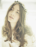 Young woman with long brunette hair in natural pose with garland of flowers on head
