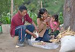 Jovita Guzman, a Maya Mam woman, pulls the grain off of corn at her home in Comitancillo, Guatemala, with help from her husband Maximilian Porfirio Garcia. Their two-year old daughter Marilisa accompanies them.
