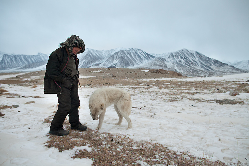A young boy with a dog..At Burgut Yor (Eagle's Nest) camp (Apendi Boi's camp)...Trekking through the high altitude plateau of the Little Pamir mountains, where the Afghan Kyrgyz community live all year, on the borders of China, Tajikistan and Pakistan.