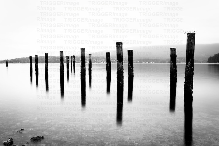 A long exposure of several posts and their reflections in the water.