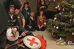 Family friends gather around the Christmas tree and watch performance of traditional English folk play The Bampton Mummers performing Christmas Eve. Bampton Oxfordshire.   UK 2008. Bold Slasher and St George, ( on ground dead )