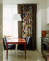 A family heirloom patchwork quilt has been made into a curtain which, through its visual impact, unites the textures and colours in this kitchen