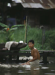 A boy baths in a klong. People live on the klongs, boulevards of water that flow through the city like open veins,  and spend their lifetimes living in houseboats in Bangkok, Thailand. (Jim Bryant Photo)....
