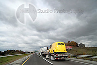 Americana Series: Road Trip<br /> <br /> Yellow Hot Rod being transported across rural landscape.