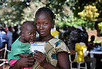 Holding her baby, Victoria John Toro displays the card she received after registering to vote on November 15, the first day of a 17-day registration period in preparation for the January 2011 referendum in Southern Sudan on secession from the north of the country. Toro registered to vote at a registration center located in a Catholic school in Yambio, in Western Equatoria State. Her index finger is stained at the end, the result of dipping it in ink, one measure designed to eliminate fraud. NOTE: In July 2011 Southern Sudan became the independent country of South Sudan.