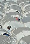 """A woman walks through a """"tent city"""" for homeless families set up in the Belair neighborhood of Port-au-Prince, Haiti, in the wake of a devastating earthquake that shook the Caribbean island nation on January 12."""