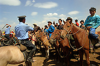Khui Doloon Khudag, Mongolia, July 2003..Competitors & spectators at the horse racing in the national Naadam 40 kilometres outside Ulaanbaatar..Mounted police hold back friends and relatives of jockeys at the end of a race.