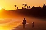Mother and daughter walking along beach, silhouetted at sunset  Santa Barbara, California USA