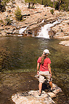 Female hiker exploring a swimming hole on Canyon Creek, Tahoe National Forest California