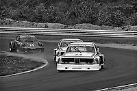Sam Posey drives his BMW 3.0 CSL ahead of BMW teammate Hans Stuck and Al Holbert in his Porsche Carrera RSR 005 0009 during the Schaefer 350 IMSA Camel GT race at Lime Rock Park near Lakeville, Connecticut, on May 26, 1975. (Photo by Bob Harmeyer).