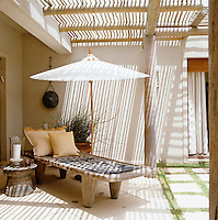 A locally made wooden sun lounger with a white parasol beneath the slatted shade of a terrace