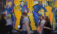 People walking past a section of the Berlin Wall depicting the painting Die Tanzenden or the Dancers by Sabine Kunz, damaged by graffiti, part of the East Side Gallery, a 1.3km long section of the Wall on Muhlenstrasse painted in 1990 on its Eastern side by 105 artists from around the world, Berlin, Germany. Picture by Manuel Cohen