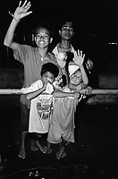 Philippines. National Capital Region. Manila. A group of children living in the streets is standing at night outside Paradise village. The young boy with a white paper bag is sniffing glue. Paradise village has a population of 15'000 people and is a part of Barangay Tonsuya situated on Lettre Road in Malabon. Manila is part of the National Capital Region (NCR) on Luzon island. Manila is the capital of the Philippines and one of the sixteen cities that comprise Metro Manila. Metro Manila is the most populous metropolitan area in the Philippines. © 1999 Didier Ruef
