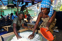 Men and women learning how to process cassava at a small factory run by Planting Promise, Newton, Freetown, Sierra Leone. Planting Promise is an organization dedicated to the development of education in Sierra Leone. Its aim is to bring opportunities to initiate self-run, self-supporting projects that offer real solutions to the difficulties facing the world's poorest country. They believe real and lasting development comes from below, from local projects that address specific needs, rather than large international models. To this end, they currently run five projects that aim to bring wealth into the country through business. The profits from these businesses are then used to support free education for children and adults...Through the combination of business with social progress, the charity hopes that they are providing real, lasting and profound changes for the better, by promoting sustainable and beneficial industry in the country, and putting it to the service to the needs of the people. As well as providing the income to fund the school, the farms will also be an example of successful commercial enterprise to teach the children in the school the viability of profit-making schemes that go beyond subsistence models, the only things the children of these desperately poor areas are accustomed to. By learning particular details of the challenges that they will face, the children will emerge from this school equipped to contribute in a real way to their society.