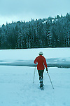 Woman snowshoeing through a meadow