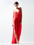 Beautiful brunette fashion model barefoot in red gown