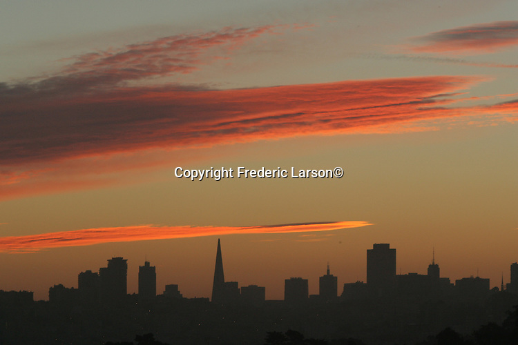 The morning clouds appear like strokes from a artist paint brush during sunrise as looking back at the San Francisco skyline, California.