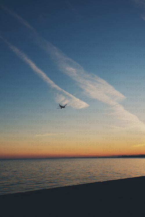 A plane flying into the sunset off the coast of Nice, France