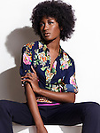Beautiful black woman with in dark blue fashionable shirt with floral design and pants sitting isolated on white background.