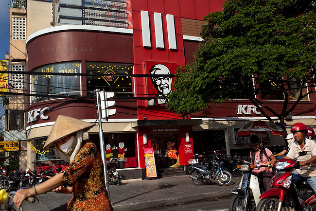 Traffic goes by a Kentucky Fried Chicken restaurant in downtown Ho Chi Minh City...Kevin German / LUCEO