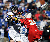 Mike Catalino (29) of Duke is checked by Ryder Bohlander (34) of Maryland during the Face-Off Classic in at M&T Stadium in Baltimore, MD