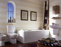 A modern bathroom with striped pattern walls and a white bathroom suite comprising washbasin, sink, toilet and bidet.