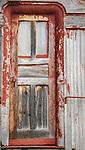 A red door still hangs on an old train car.