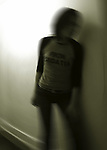 A blurred image of a figure standing in an empty hallway