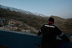 A man on the rooftop of his house overlooking the Israel-Syria border, at the Druze village of Majdal Shams, Golan Heights.