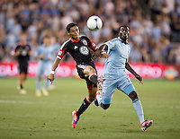 Andy Najar (14) of D.C. United clears the ball away from C.J. Sapong (17) of Sporting Kansas City during the game at Livestrong Sporting Park in Kansas City, Kansas.  D.C. United lost to Sporting Kansas City, 1-0.