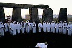Druids celebrate the summer solstice at Stonehenge Wiltshire June 21st dawn sunrise. England. Perform traditional rituals and rites.