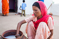 Suki (not her real name), churns milk while her son plays in the courtyard of her house in Jhaju village, Bikaner, Rajasthan, India on 4th October 2012. Now 20, Suki was married off at age 12, but only went to live with her husband when she was 14. The three sisters, aged 10, 12, and 15 were married off on the same day by their maternal grandfather while their father was hospitalized. Her husband died three years after she moved in, leaving her with a daughter, now 6, and a son, now 4. She has no parents-in-laws and thus returned to her parents house after being widowed because her brother-in-law, who had become the head of the family after his brother's death, had refused to allow Suki to inherit her deceased husband's fair share of agriculture land. Although Suki's father wants her to remarry, she refuses to, hoping instead to be able to support her family through embroidery and tailoring work. The family also makes hand-loom cotton to subsidize their collective household income. Photo by Suzanne Lee for PLAN UK