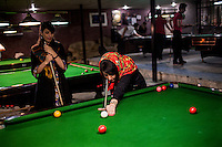 Women play pool in a men only gym, which it is forbidden for women to enter.
