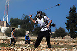 A Palestinian protester hurls a stone at Israeli security forces during a protest against the expansion of the nearby Jewish settlement of Halamish, in the West Bank village of Nabi Saleh near Ramallah, Friday, Nov. 30, 2012. Photo by Issam Rimawi