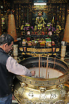 Bao-jhong Yi-min Temple, Kaohsiung -- Temple custodian cleaning the joss stick brazier of incense ash.