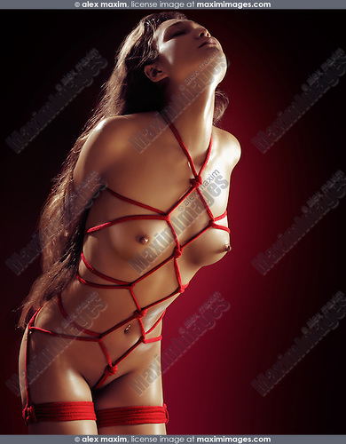 Beautiful naked asian woman tied up with red ropes. Sensual Japanese bondage Shibari, Kinbaku, artistic nude photo.
