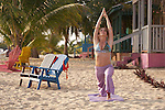 Belize, Central America - Woman practices yoga by a beach house on the end of the Placencia spit.