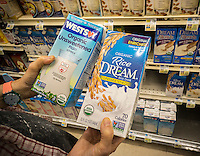 A shopper considers packages of WestSoy soy milk and Rice Dream rice drink, both brands of Hain Celestial, in a supermarket in New York on Wednesday, August 17, 2016. Hain Celestial Group is being investigated because of an issue in their accounting which may have booked revenue into a quarter where it was not supposed to be.  (© Richard B. Levine)