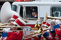 FDNY firefighter watches IS 318 marching band in the annual Three Kings Day Parade in the Bushwick neighborhood of Brooklyn on Sunday, January 8, 2012. Neighborhood school children marched with residents, camels and kings in their celebration of the Epiphany. Many in the Latino community celebrate the traditional December 25 Christmas and the Epiphany. (© Richard B. Levine)