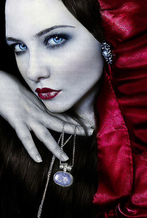 A portrait of a pale caucasian girl with a red hood holding a necklace looking at the camera