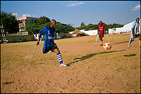 """Angola, May 2006.A match between the top 2 teams in the Angola handycapped football championship.""""3 de Decembre"""" (Disability Day, in red ) plays against """"11 de Novembre"""" (Angola Independence Day, in blue).  Just 4 years after the end of a 25 year long civil war, Angola is starting to emerge again, yet a lot remains to be done: entire regions are still cut-off from the ouside world because of landmines and broken bridges, over 80% of the population lives below the poverty threshold in one of the potentially richest country in Africa. Natural ressources include oil, diamonds, gold and...water!.Malaria, tuberculosis, HIV/Aids are endemic, cholera and meningitis frequent."""
