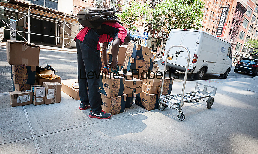 A deliveryman sorts packages from the meal delivery startup Blue Apron in front of an apartment building in Chelsea in New York on Monday, June 20, 2016. Blue Apron is reported to be considering an initial public offering in 2017. (© Richard B. Levine)