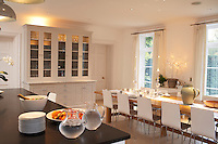 The long kitchen table and cupboards were specially made for the room and a white linen runner and placemats give the kitchen a Scandinavian feel