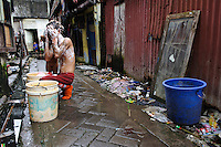 A man and child washing themselves on a street, Tallo, Makassar, Sulawesi, Indonesia.