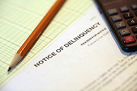 Notice of Deliquency Paperwork with Calculator and Graph Paper