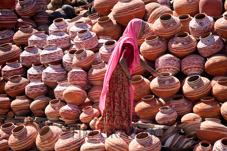 Indian woman selling clay water pots on sale in old town Udaipur, Rajasthan, Western India,