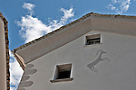 The symbol of the Ibex, mountain goat, which is the symbol of the Grabunden canton, on a house in the town of Castasegna, a Swiss town right on the border with Italy in the Bregaglia Valley. The borders around the door are patterns scratched out of the still wet wall, decorative artwork called sgraffiti, traditionally done in two colors and originating in Italy, brought to the Engadin region of Switzerland in the 16th century and is still used today