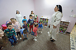 Sister Ferdos Zora jumps with students as they sing in a preschool for displaced children run by the Dominican Sisters of St. Catherine of Siena in Ankawa, near Erbil, Iraq.<br /> <br /> The children, and the nuns themselves, were displaced by ISIS from Mosul and Qaraqosh in 2014. The sisters have established a variety of schools and other ministries among the displaced.